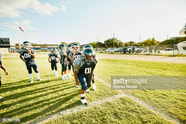 Young football player preparing to run passing drill during football practice with teammates