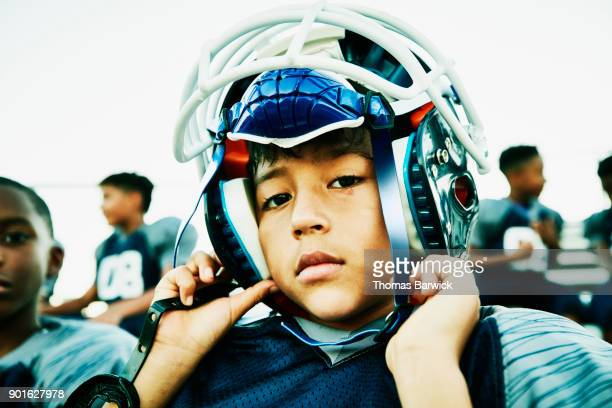 Young football player putting on helmet while sitting with teammates before game