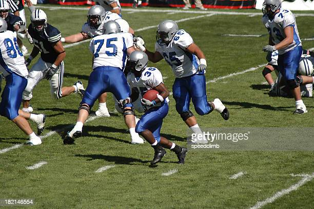 young football player rushing for a touchdown - quarterback stock pictures, royalty-free photos & images