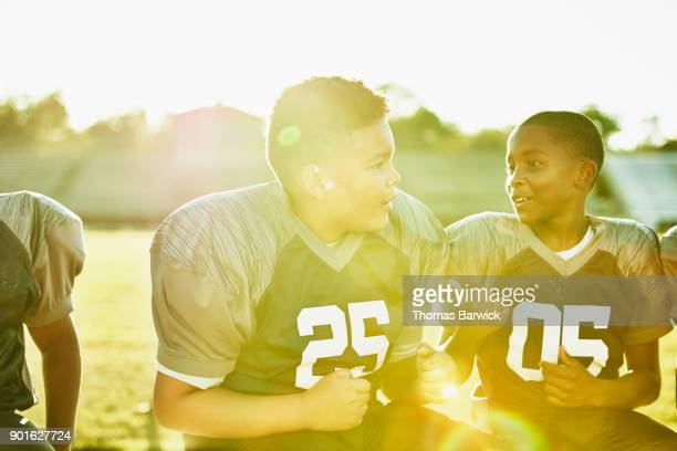 Young football player sitting on bench with teammates before football game