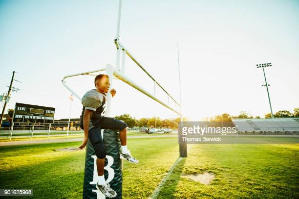 Young football player sitting on goal post on football field after practice