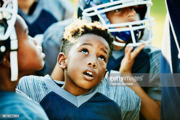 Young football player standing with teammates before game listening to coach