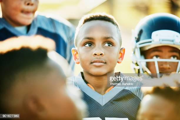 Young football player standing with teammates listening to coach