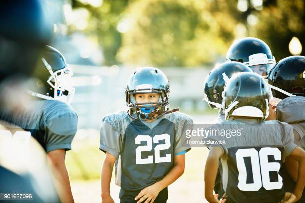 Young football player standing with teammates on field during practice
