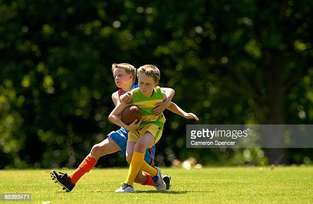 young football player tackles opposition - afl stock pictures, royalty-free photos & images