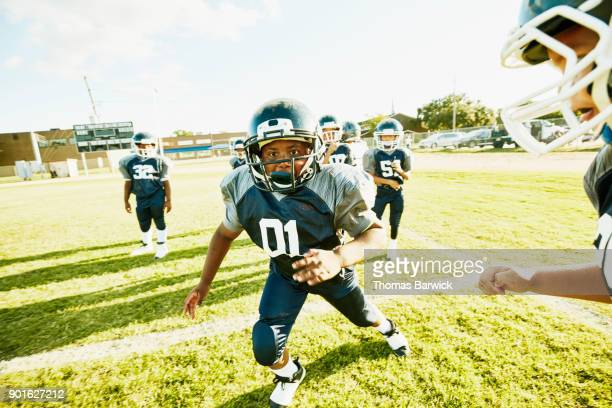 young football player trying to run past teammate during passing drill in football practice - rush fútbol americano fotografías e imágenes de stock