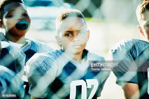 Young football player waiting behind fence with teammates before game