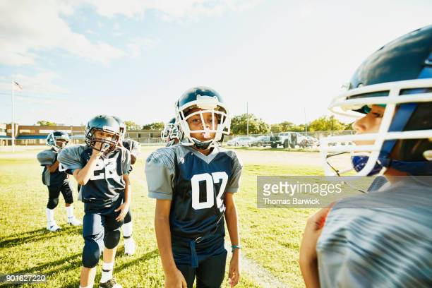 Young football player waiting to run passing drill against teammate during practice