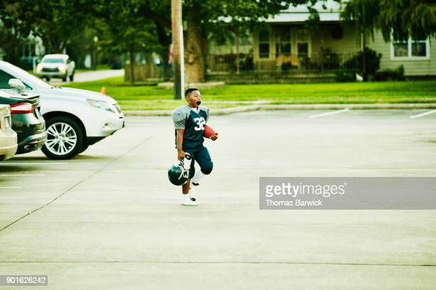 young football player walking across parking lot before football game - american football uniform stock pictures, royalty-free photos & images