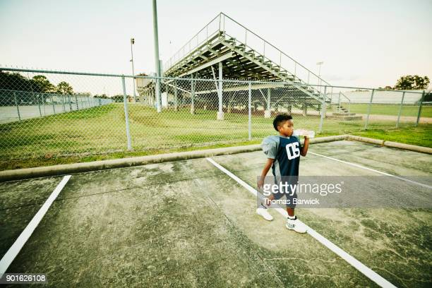 Young football player walking through stadium parking lot drinking water after football game
