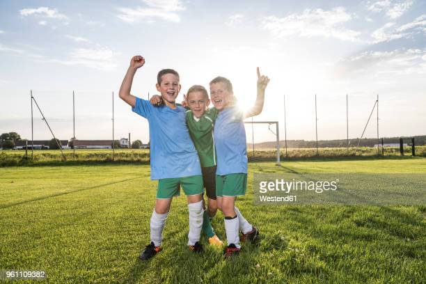 young football players cheering on football ground - divisa sportiva foto e immagini stock