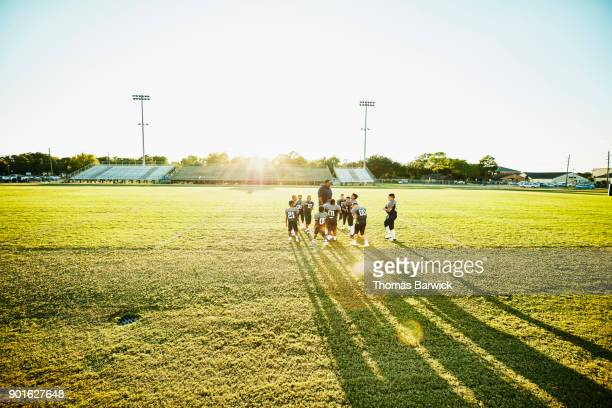 Young football players gathered around coach on field after football practice