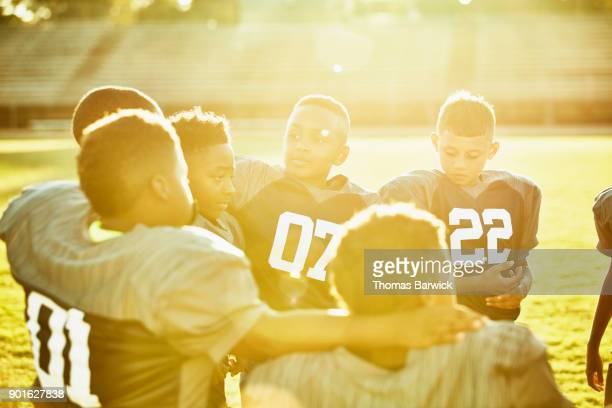 Young football players gathered together with arms on shoulders on field after football game