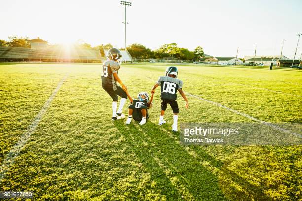 Young football players helping teammate up during practice on football field