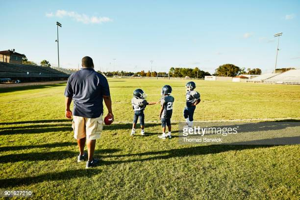 Young football players running a drill during practice with coach