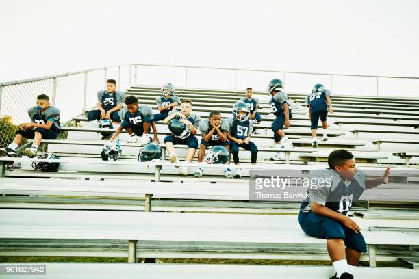 Young football players seated together on stadium bleachers before football game