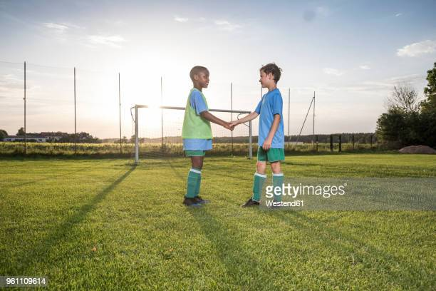 young football players shaking hands on football ground - fair play sport foto e immagini stock