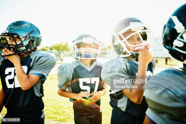 Young football players standing on field during practice listening to instructions from coach