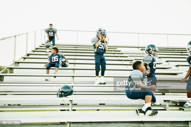Young football teammates gathering on bleachers after football game
