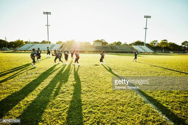 Young football teammates playing together on field after football practice