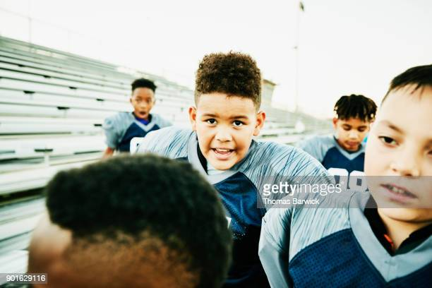 Young football teammates preparing to take field to warm up before football game