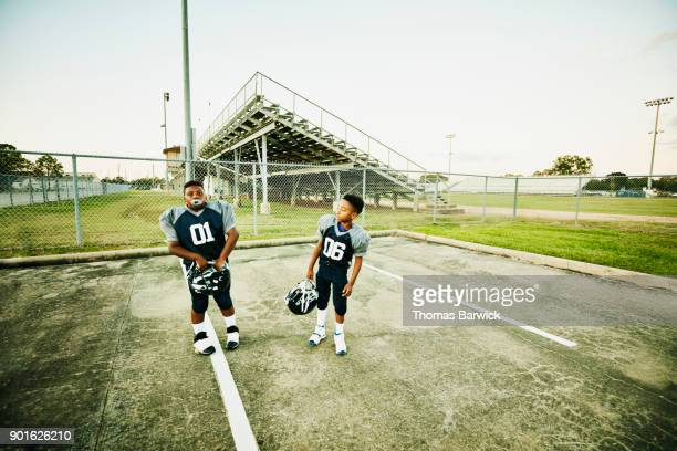 Young football teammates standing in stadium parking lot after football game
