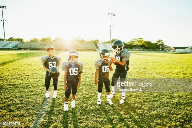 Young football teammates standing on field preparing for practice