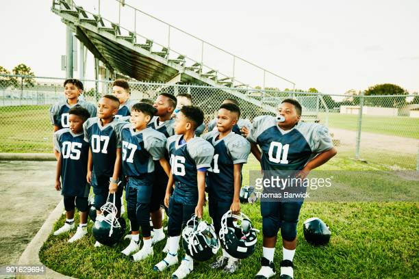 Young football teammates standing together for team portrait after football game