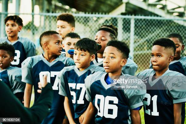 Young football teammates standing together listening to coach before football game