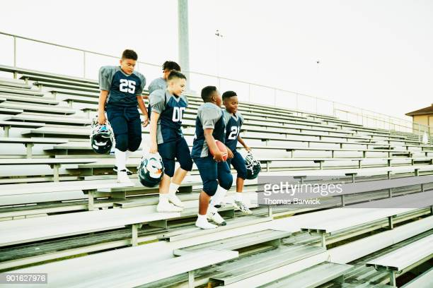 Young football teammates walking down bleacher steps after football game