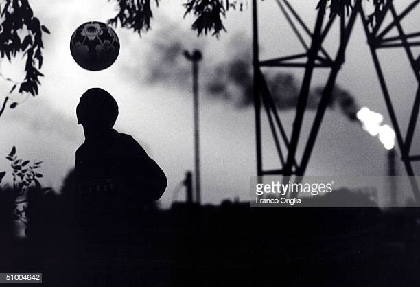 A young footballer involved with Inter Campus Project juggles a ball in front of an oil refinery April 15 2002 in Abadan Iran Inter Campus is a...