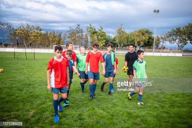 jóvenes futbolistas y entrenadores que salen del campo después de la práctica - campamento de entrenamiento deportivo fotografías e imágenes de stock