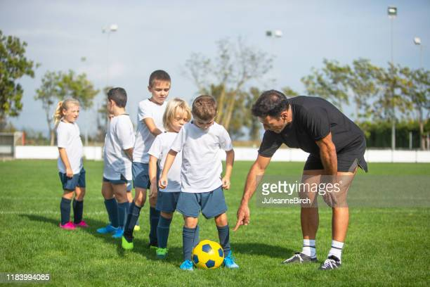 young footballers practicing ball control with coach - sports training camp stock pictures, royalty-free photos & images