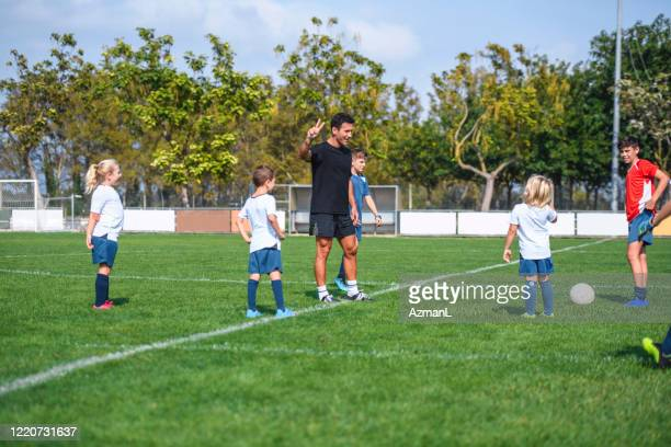 young footballers practicing on sports field with coach - sports training camp stock pictures, royalty-free photos & images