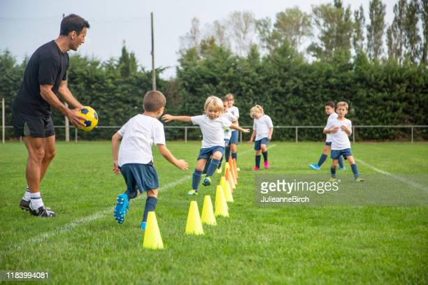 young footballers practicing running drills during practice - coach stock pictures, royalty-free photos & images