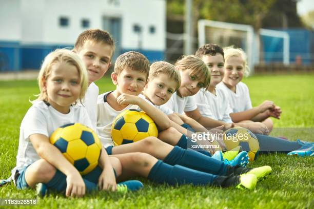young footballers sitting together at sports training camp - sports training camp stock pictures, royalty-free photos & images