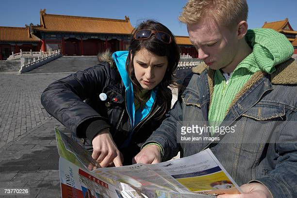 A young foreign couple points to a map, appearing puzzled, in front of the Forbidden City in Beijing.