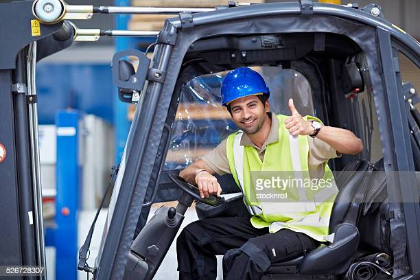 Young forklift driver giving thumbs up