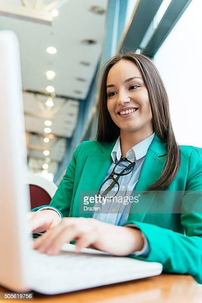 Joven caucásica businesswoman escribir formal en nueva laptop y sonriendo