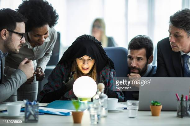 young fortune teller predicting the future for business team. - wizard stock pictures, royalty-free photos & images