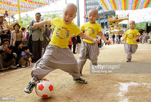 Young four and fiveyearold children play a friendly game of soccer underneath colorful hanging paper lanterns at the Chogye Temple on May 15 2010 in...