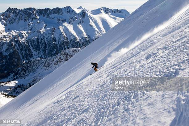 Young free skier riding down a steep off-piste terrain