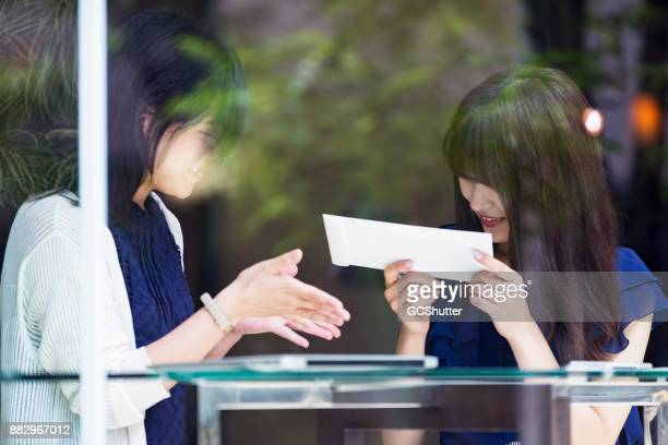 Young freelance Japanese girl receiving her first pay check and bowing with respect