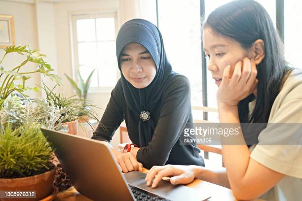 young freelancer asian muslim woman working and discussion each other on a laptop computer at cozy cafe - religion stock pictures, royalty-free photos & images