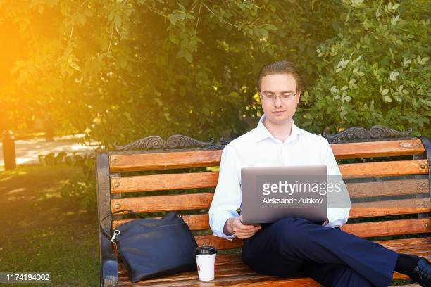 a young freelancer in a white shirt and glasses is working in the park. - white shirt stock pictures, royalty-free photos & images