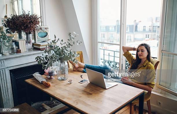 若いフリーランスくつろいでいる女性で自分のパリのアパートメント