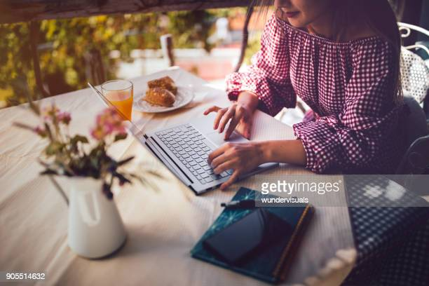 Young freelancer woman using laptop and working online outdoors