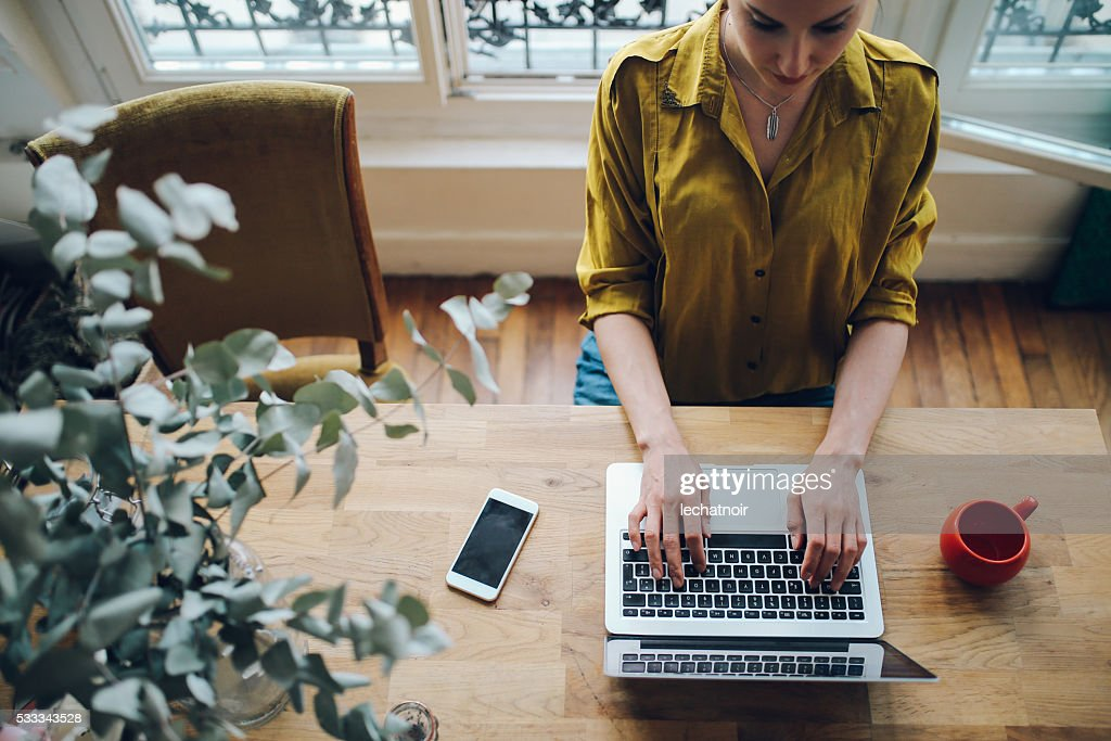 Young freelancer woman working in her Parisian apartment : Stock Photo