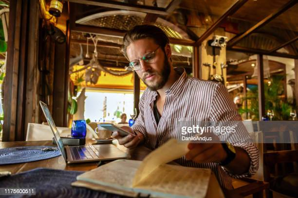 young freelancer working remotely even on vacation - handsome people stock pictures, royalty-free photos & images