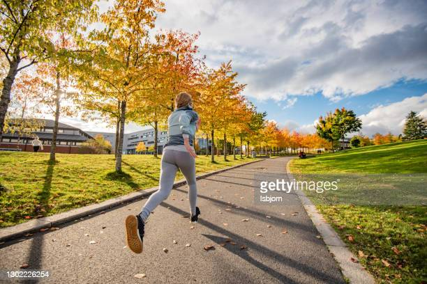young fremale running in the park at sunny autumn day. - silver shoe stock pictures, royalty-free photos & images